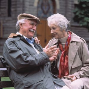 Old Couple sitting on bench enjoying their pension